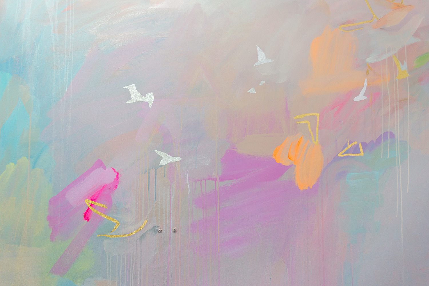 Close up of pastel abstract mural, featuring gold and silver gilded birds flying across the wall.