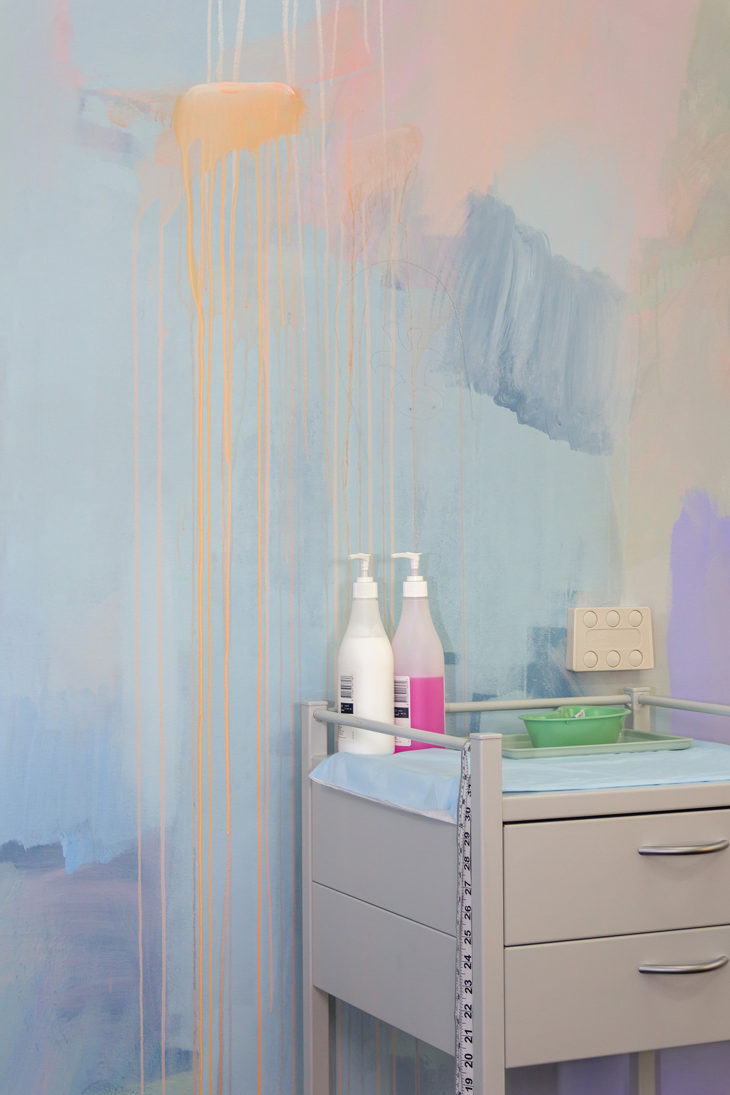 Close up detail of abstract pastel mural featuring dripping paint and medical equipment.