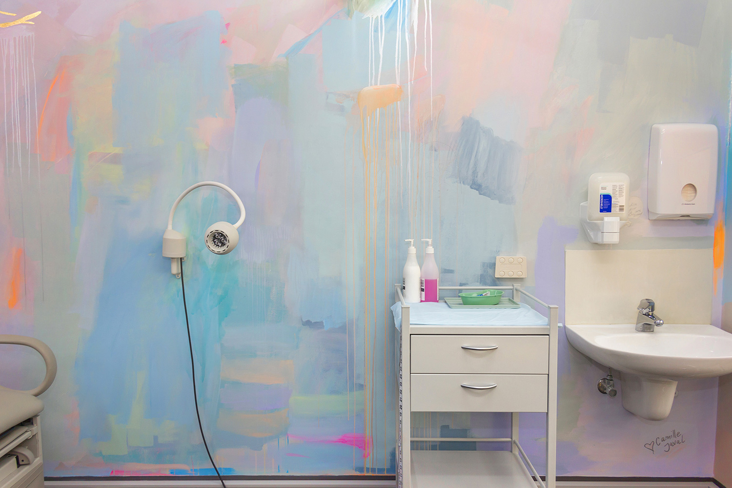 Pastel abstract mural painted in an OB/GYN office, featuring medical equipment and styled furniture.