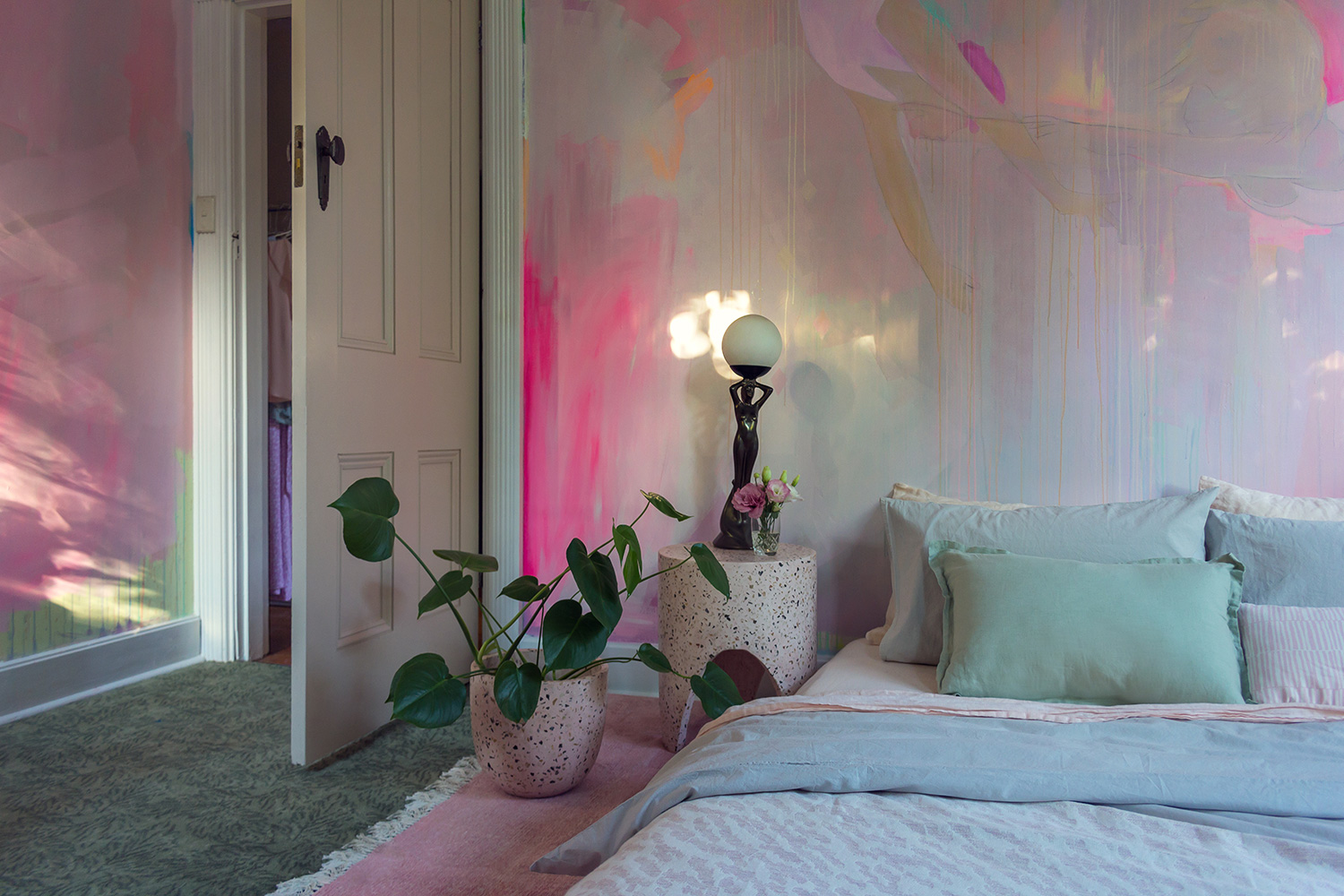 Romantic pink bedroom styled with pastel linen, plants and pink terrazzo stump. Sunlight casts pretty reflections on the abstract mural feature wall.