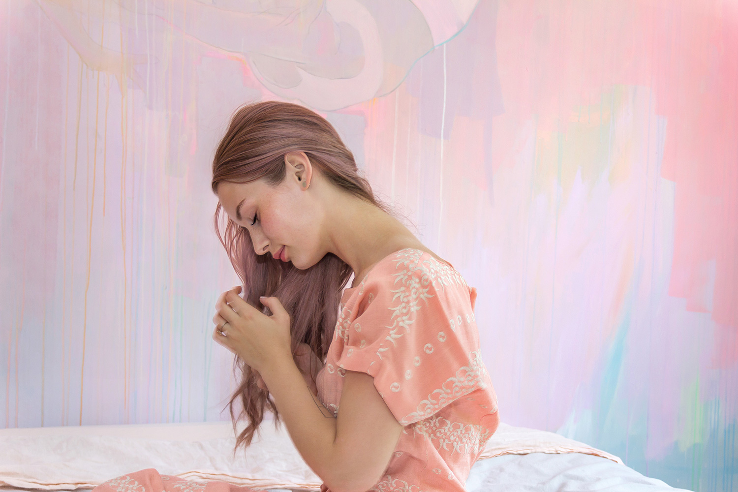 Model braids her pastel purple hair in front of an abstract mural, she wears a vintage peach dress.