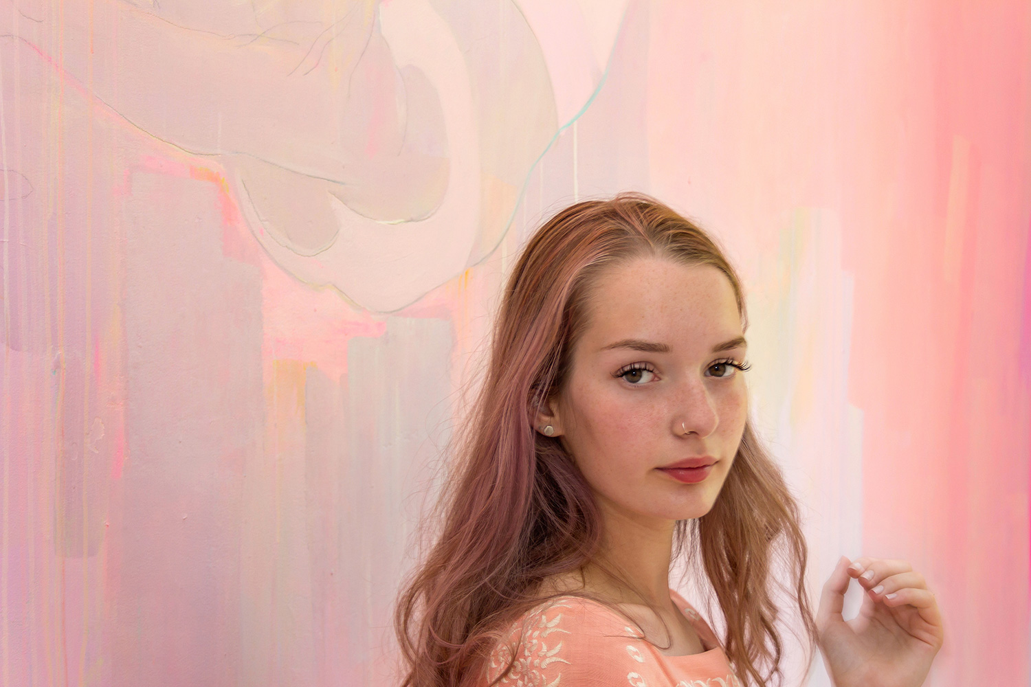 Pink pastel mural provides a pretty backdrop for this pastel haired model's portrait.