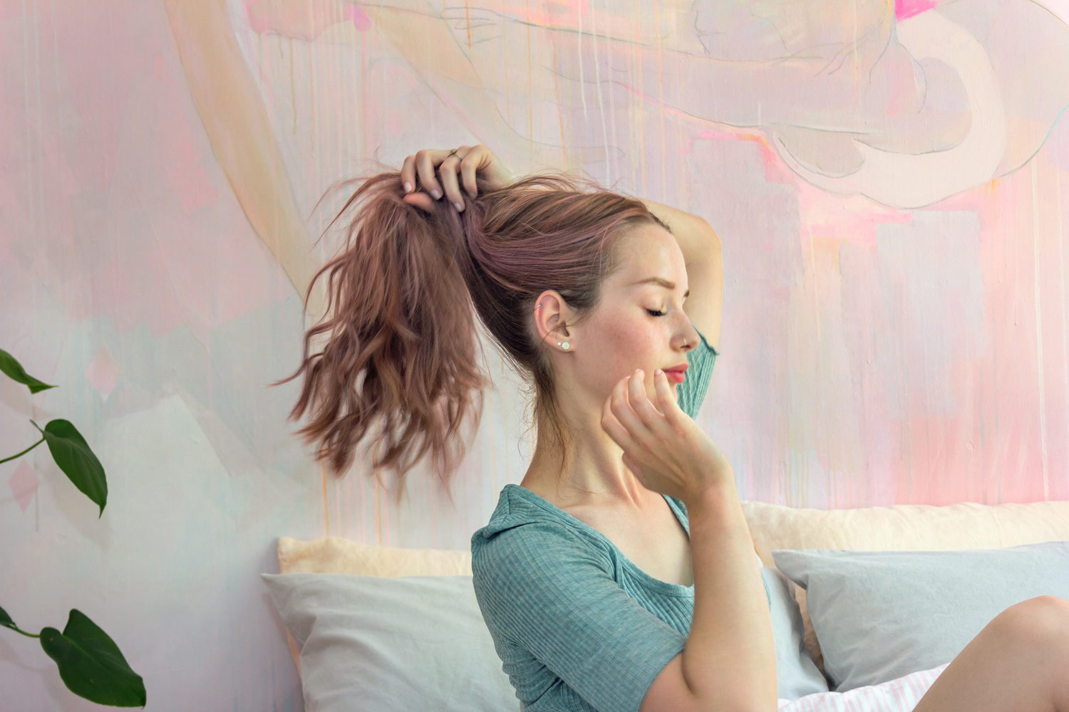 Model plays with her pastel purple hair in front of an abstract mural.