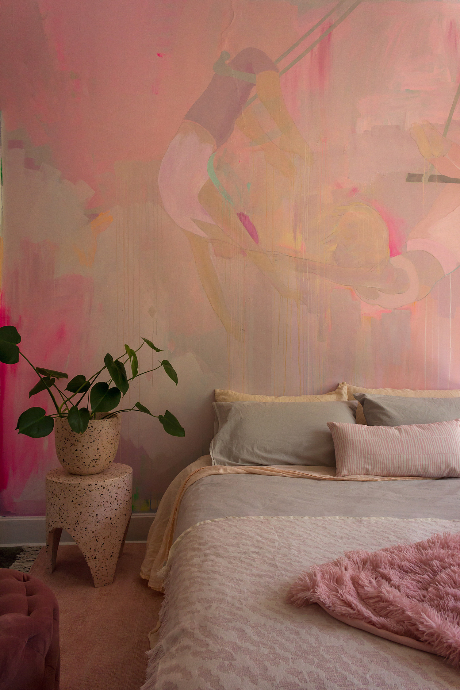 Romantic pink bedroom featuring a unique hand painted mural of two trapeze artists. The bedroom is styled with pastel linen, plants and pink terrazzo stump.