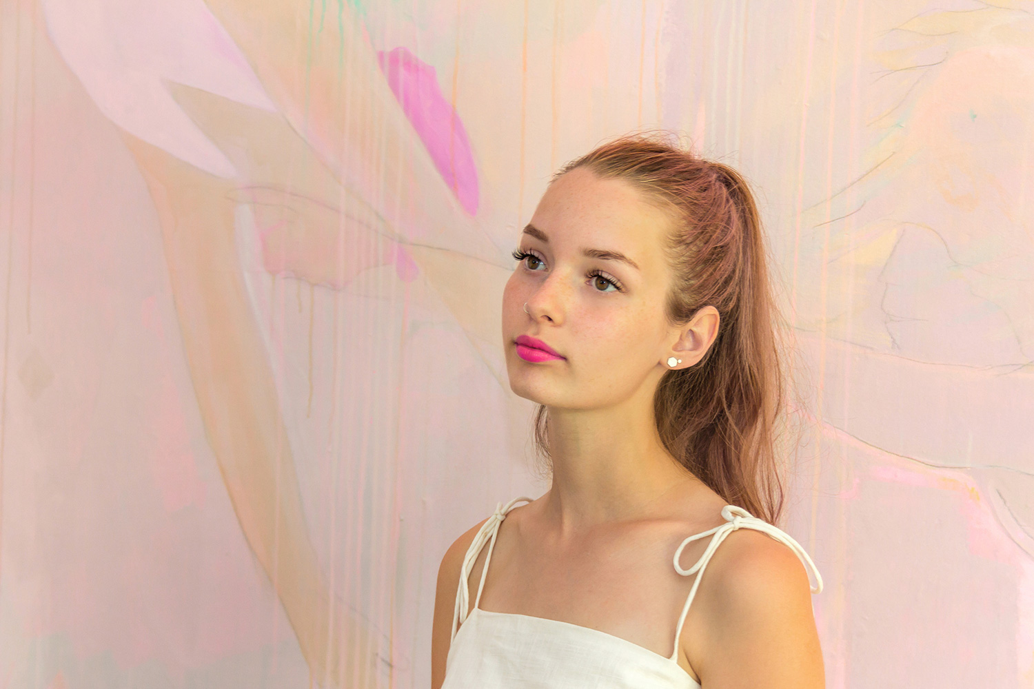 Dreamy portrait of young model with pastel hair, her bright pink lipstick pops against the soft colors of the abstract mural behind her.