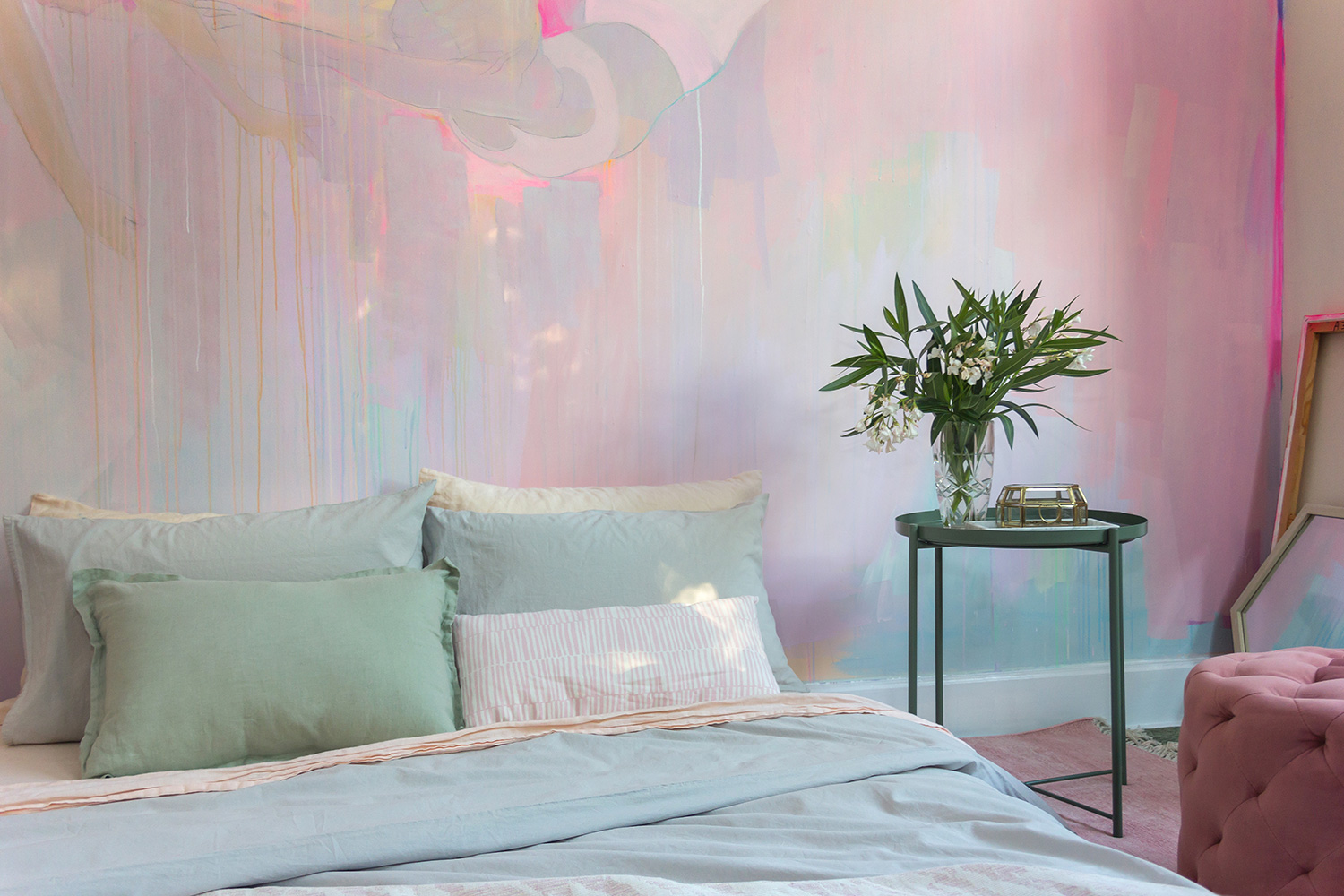 Romantic pink bedroom featuring a unique hand painted mural of two trapeze artists. The bedroom is styled with pastel bedding and flowers, with sunlight casting pretty patterns on the wall.