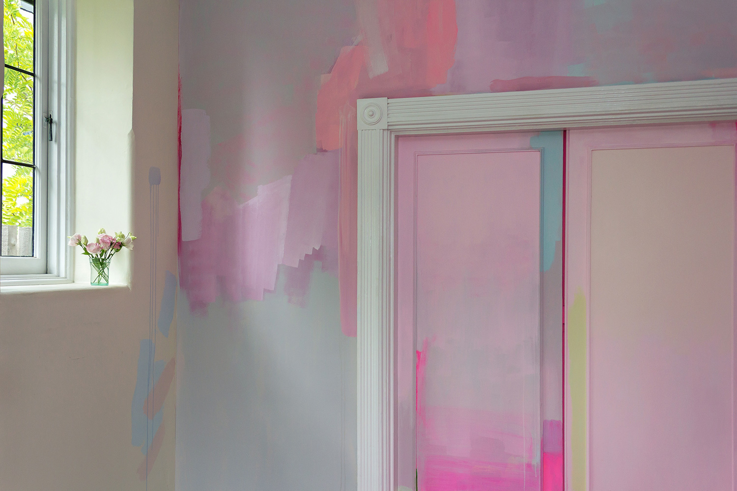 Modern abstract mural features splashes of pastel paint and pops of neon color, pink flowers on the windowsill provide contrast to the flat color.