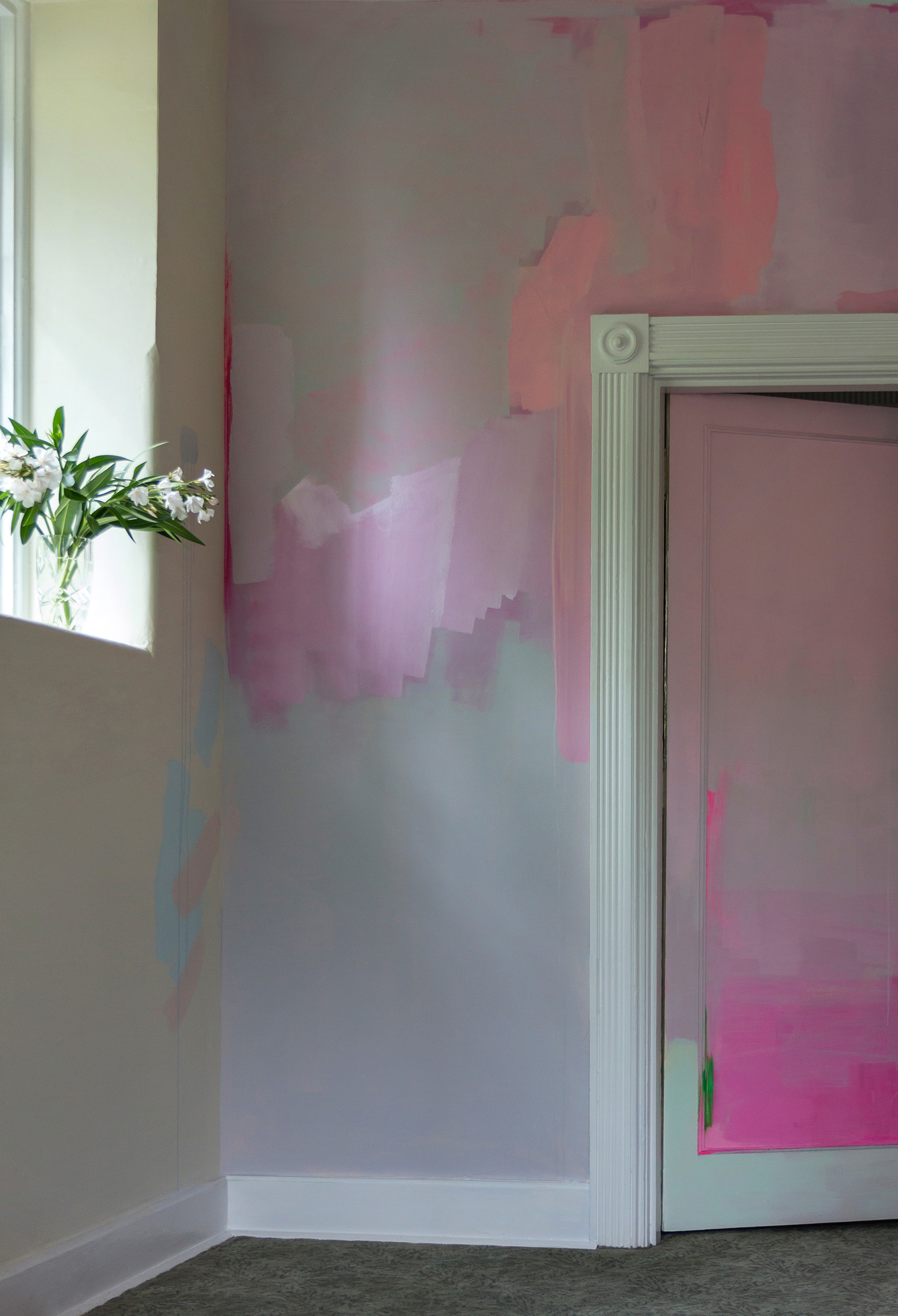 Contemporary hand painted mural features splashes of pastel paint and pops of neon, foliage on the windowsill contrasts with the flat color.