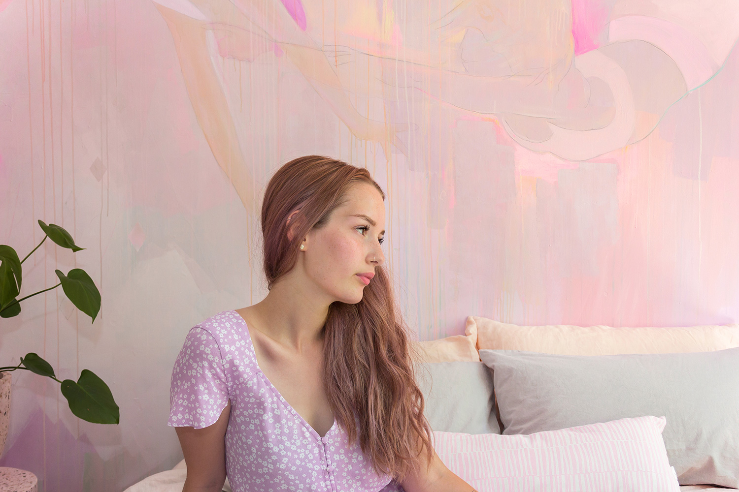 Gentle portrait of young model, the colors of her pastel hair and purple jumpsuit blend in with the soft colors of the abstract mural behind her.