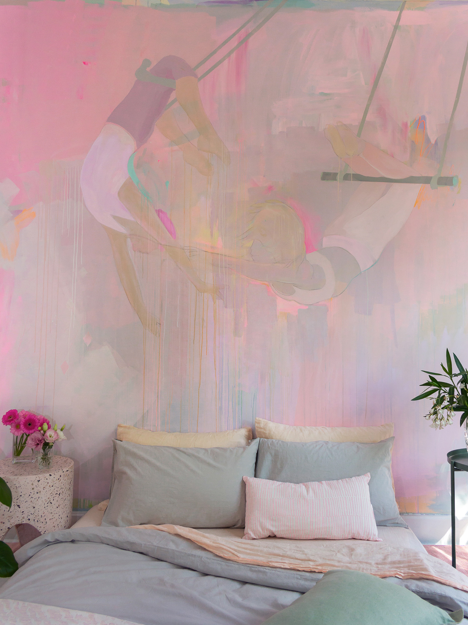 Modern pink bedroom featuring a unique hand painted abstract mural with two trapeze artists. The bedroom is styled with pastel bedding, flowers and pink terrazzo stump.