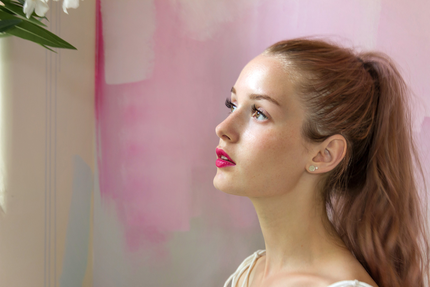 Dreamy portrait of young model, sunlight from nearby window illuminates her skin. The model's bright pink lipstick pops against the soft colors of the abstract mural behind her.
