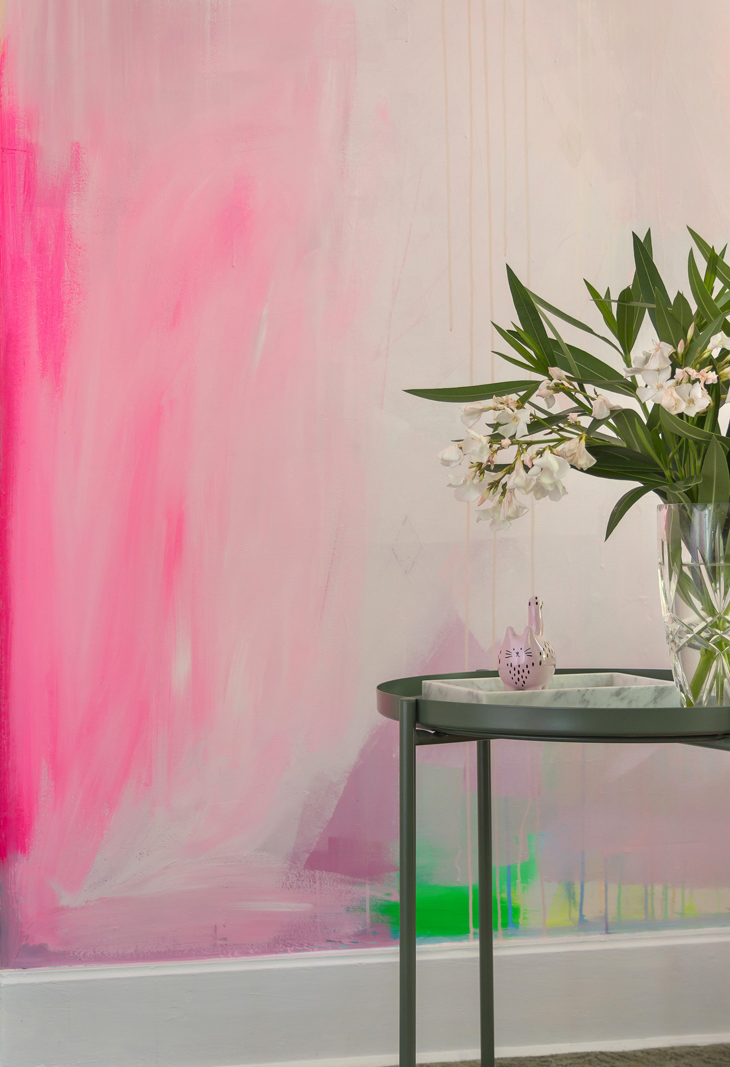 Modern abstract mural features splashes of pastel paint and pops of neon pink and green. Sage green table with foliage is styled in front of the mural.