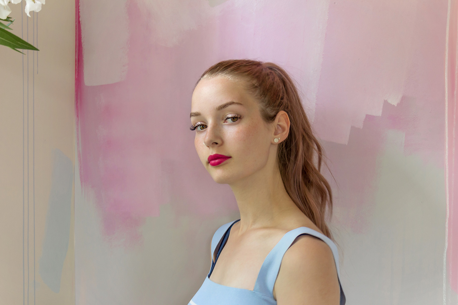 Striking portrait of young model standing in front of a modern hand painted backdrop. The model's bright pink lipstick pops against the soft colors of the abstract mural behind her.