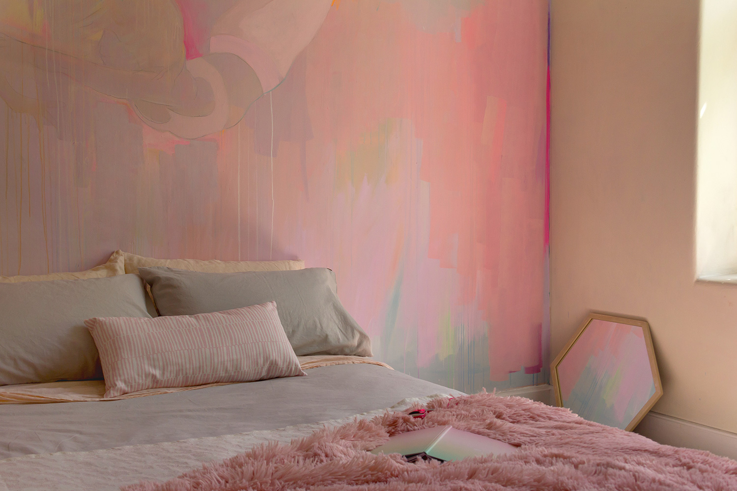 Modern abstract bedroom mural features splashes of pastel paint and pops of neon color, the bedroom glows with afternoon light.
