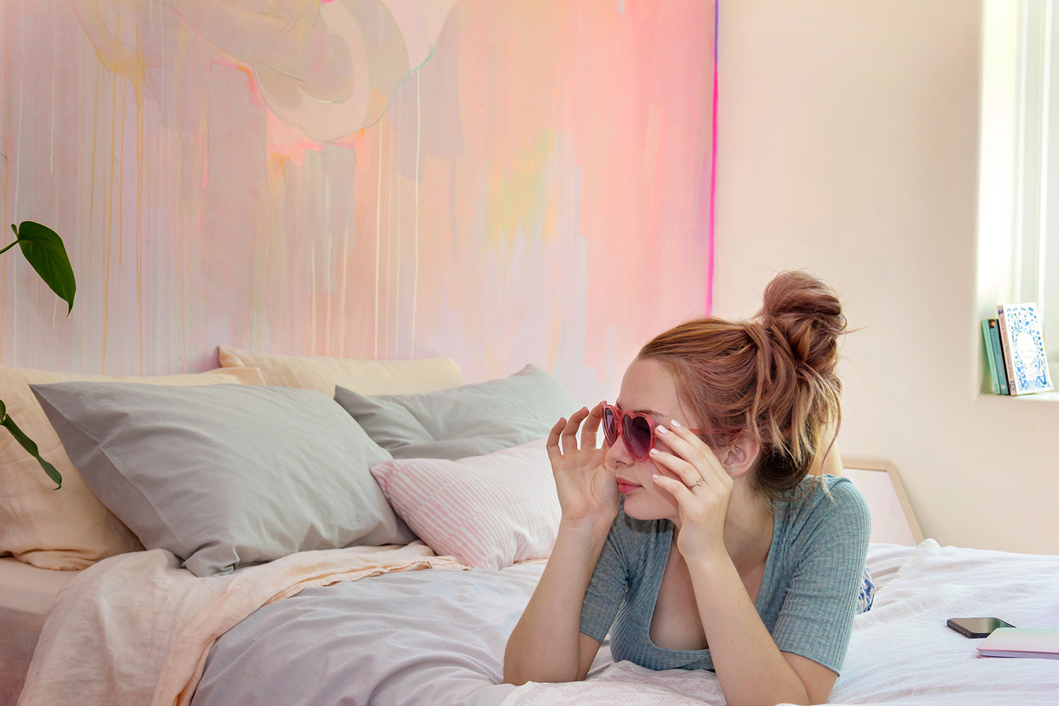 Abstract pastel mural provides a pretty backdrop for this model as she relaxes on the bed wearing love heart sunglasses.