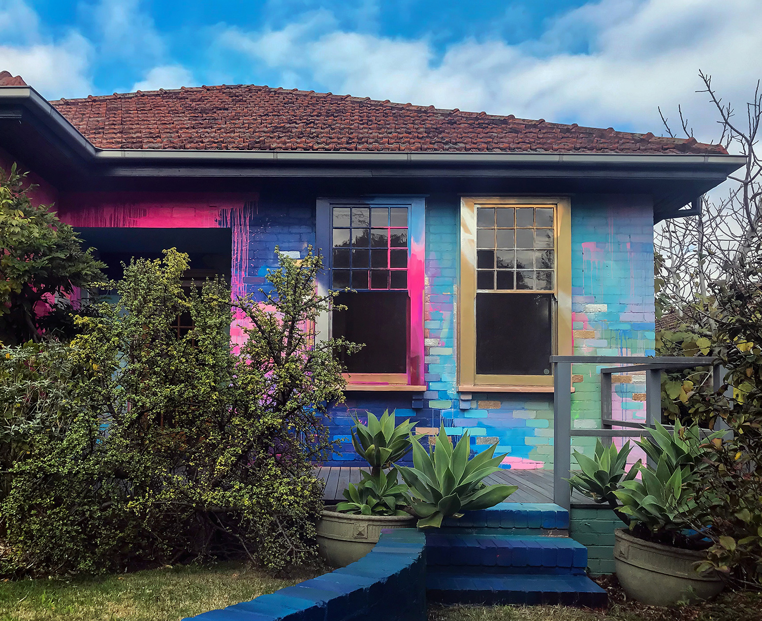 Vibrant abstract mural painted on the exterior of a house. The colors contrast with the traditional architecture of the house and surrounding natural elements.