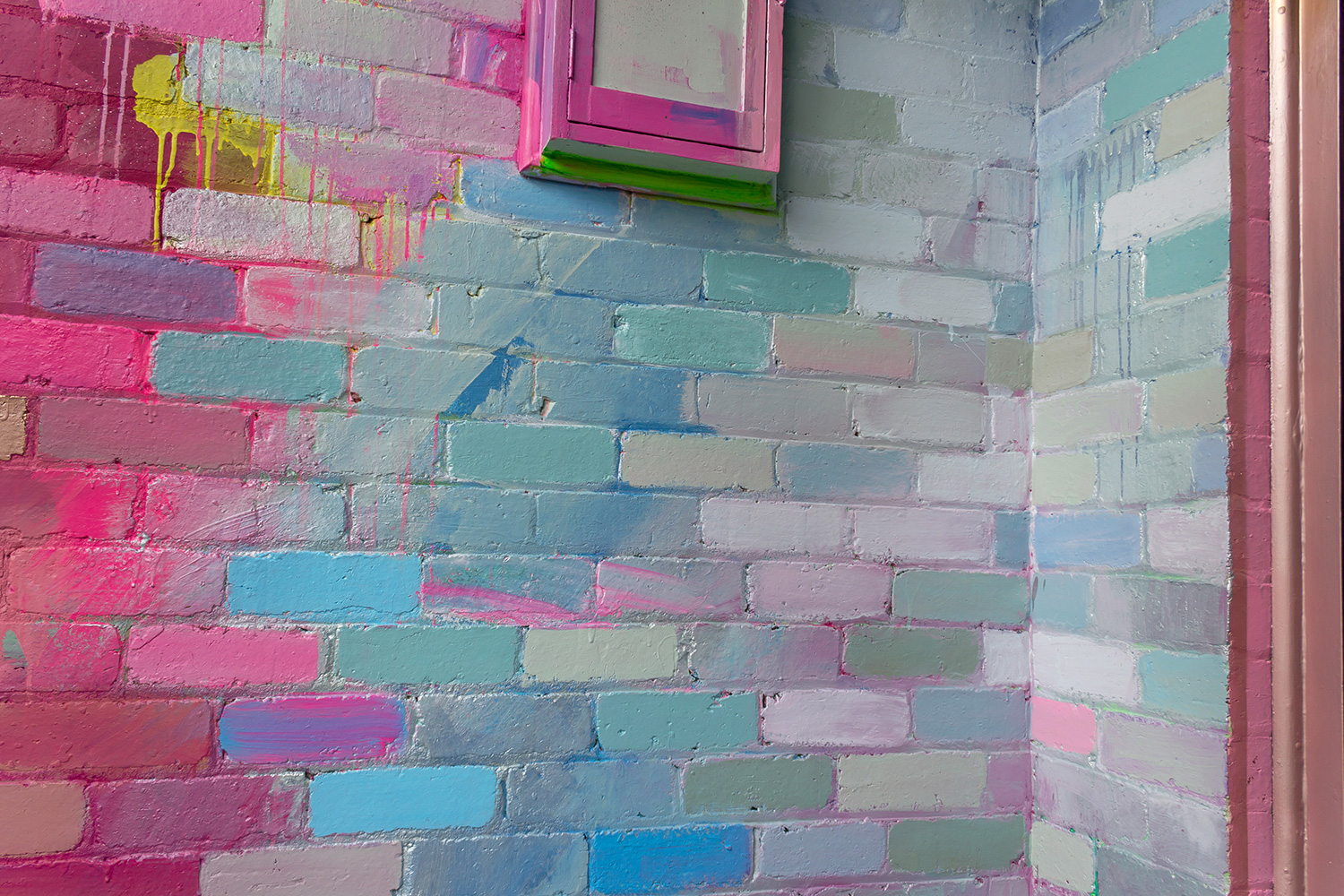 Close up wall detail of abstract mural, showing pink and blue bricks.