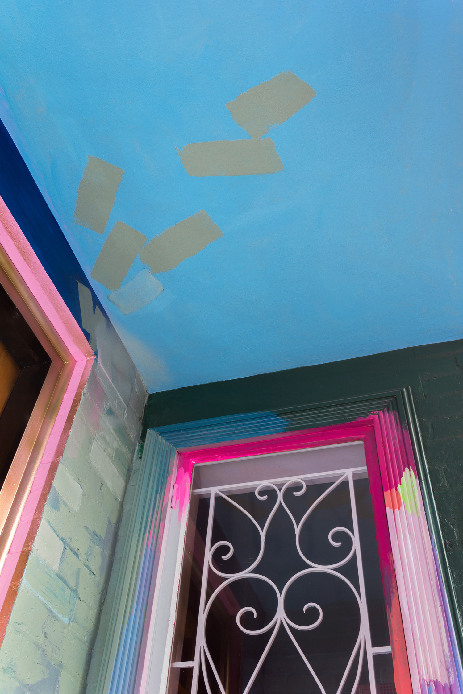 A residential home has been used as a giant art canvas, with a vibrant, abstract design painted on the bricks and window frames. The painted marks move across the walls and along the ceiling.