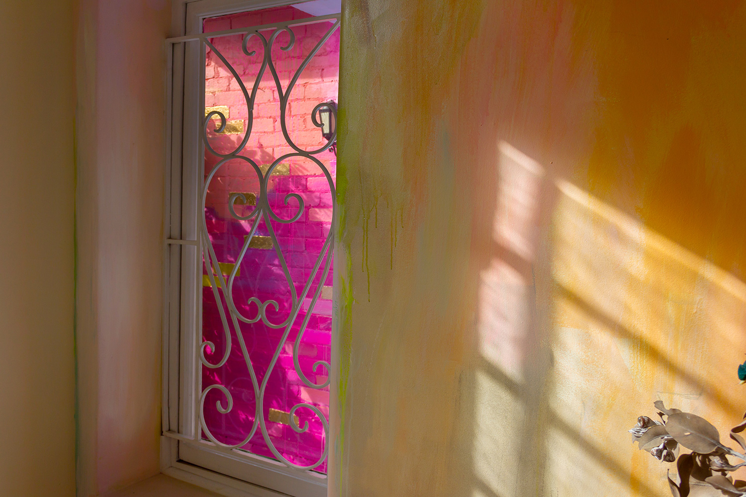 A window provides a peek at the bright pink abstract mural on the wall outside.