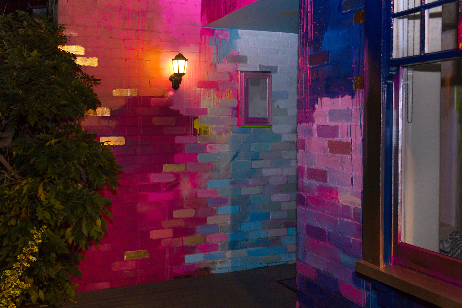 Night time glimpse at large abstract mural painted on the exterior of a house, the wall lamp lights up the metallic colored bricks.