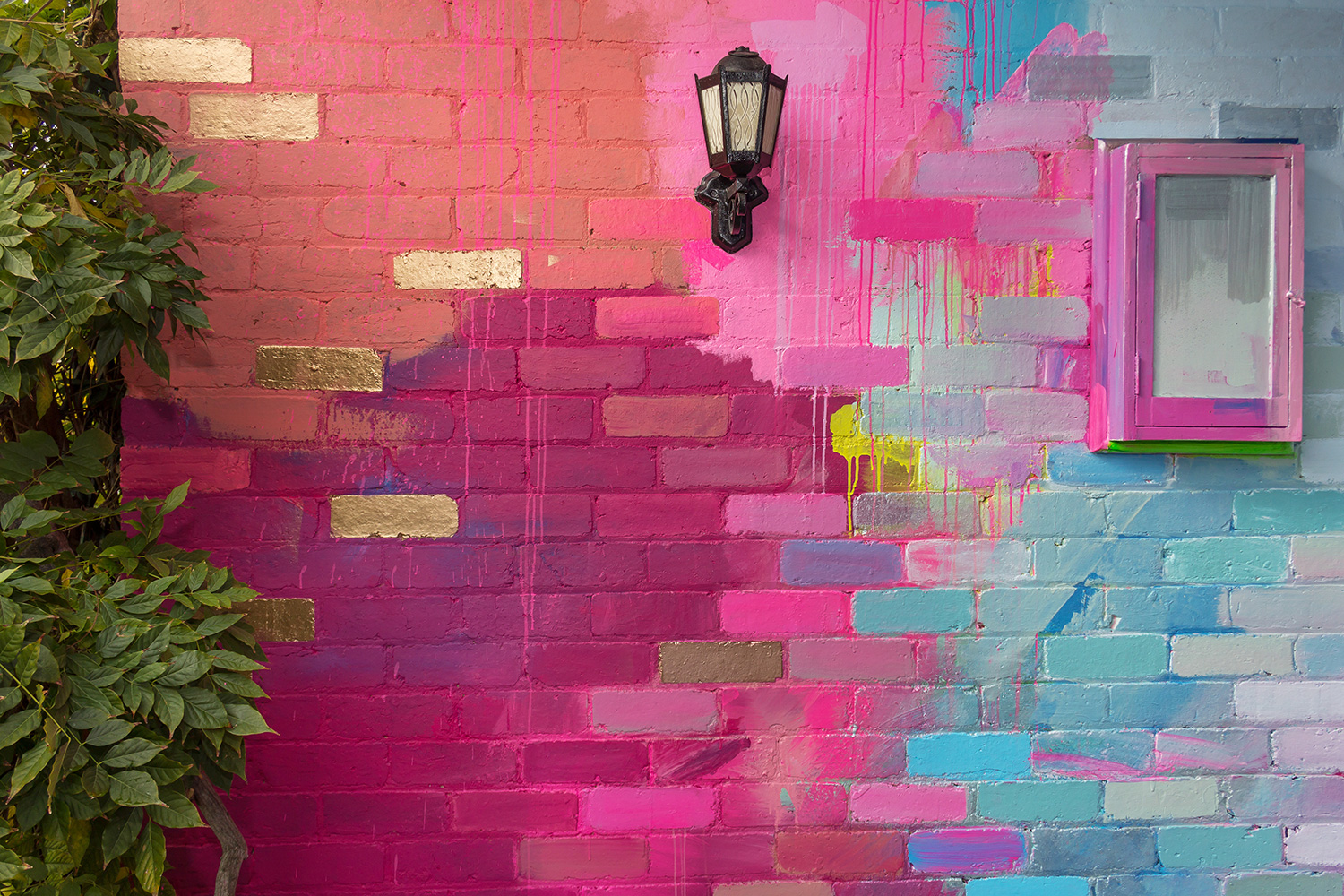 A residential home has been used as a giant art canvas, with a vibrant, abstract design painted on the bricks in a color palette of pink, blue and metallic.