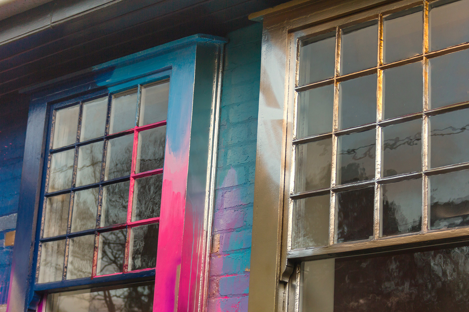 Close up of two windows that have been painted as part of a giant abstract installation on the outside of a residential property.