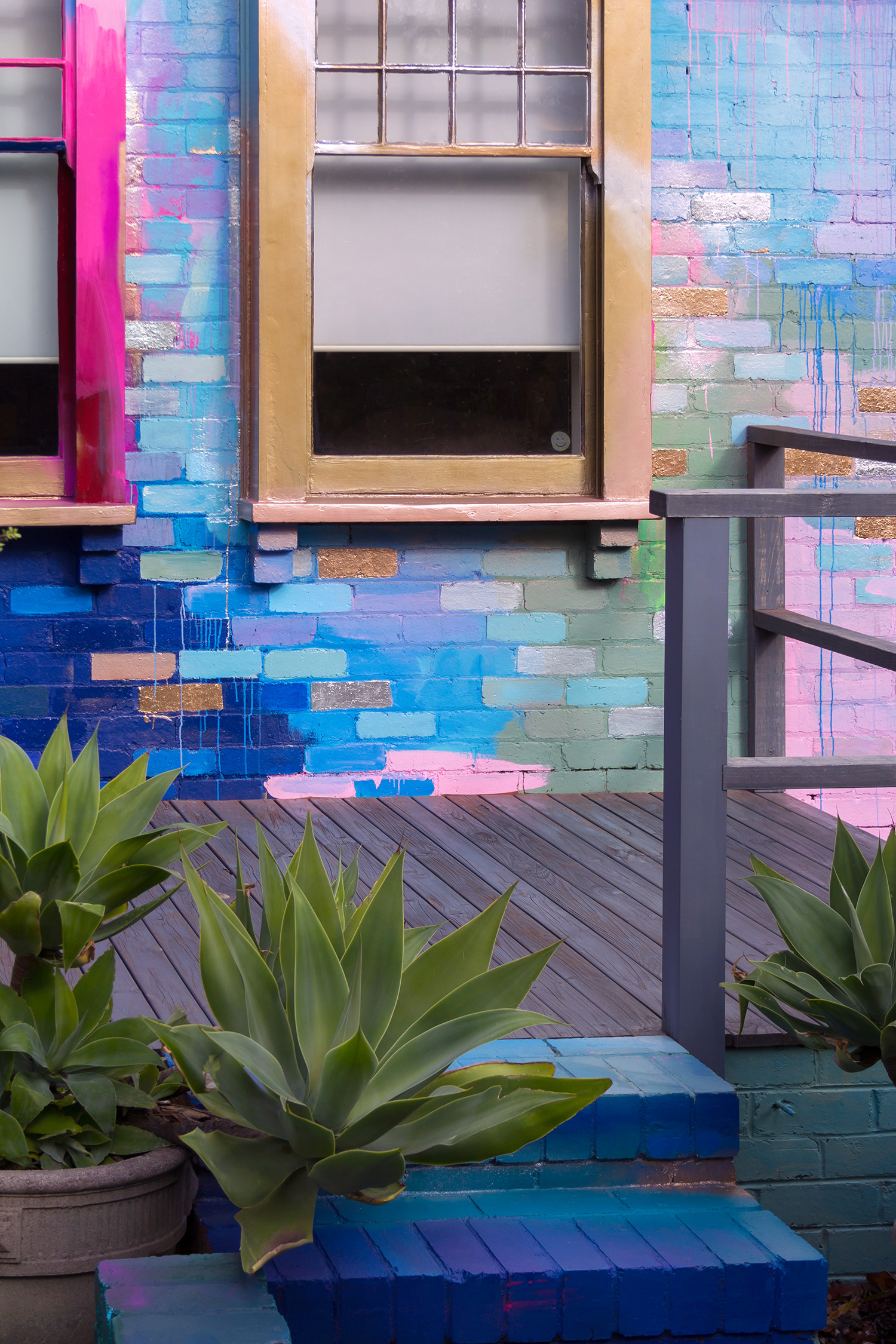 Vibrant abstract exterior mural in a bold color palette, the surrounding stairs have been painted to create a sense of entering the artwork.