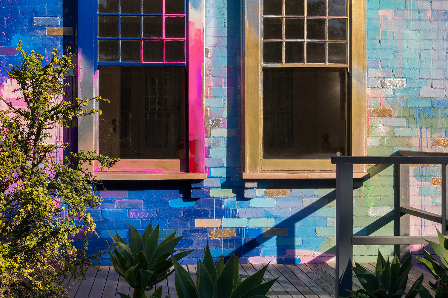 Vibrant abstract exterior mural in a bold color palette. The sun casts shadows onto the canvas, adding another visual dimension.