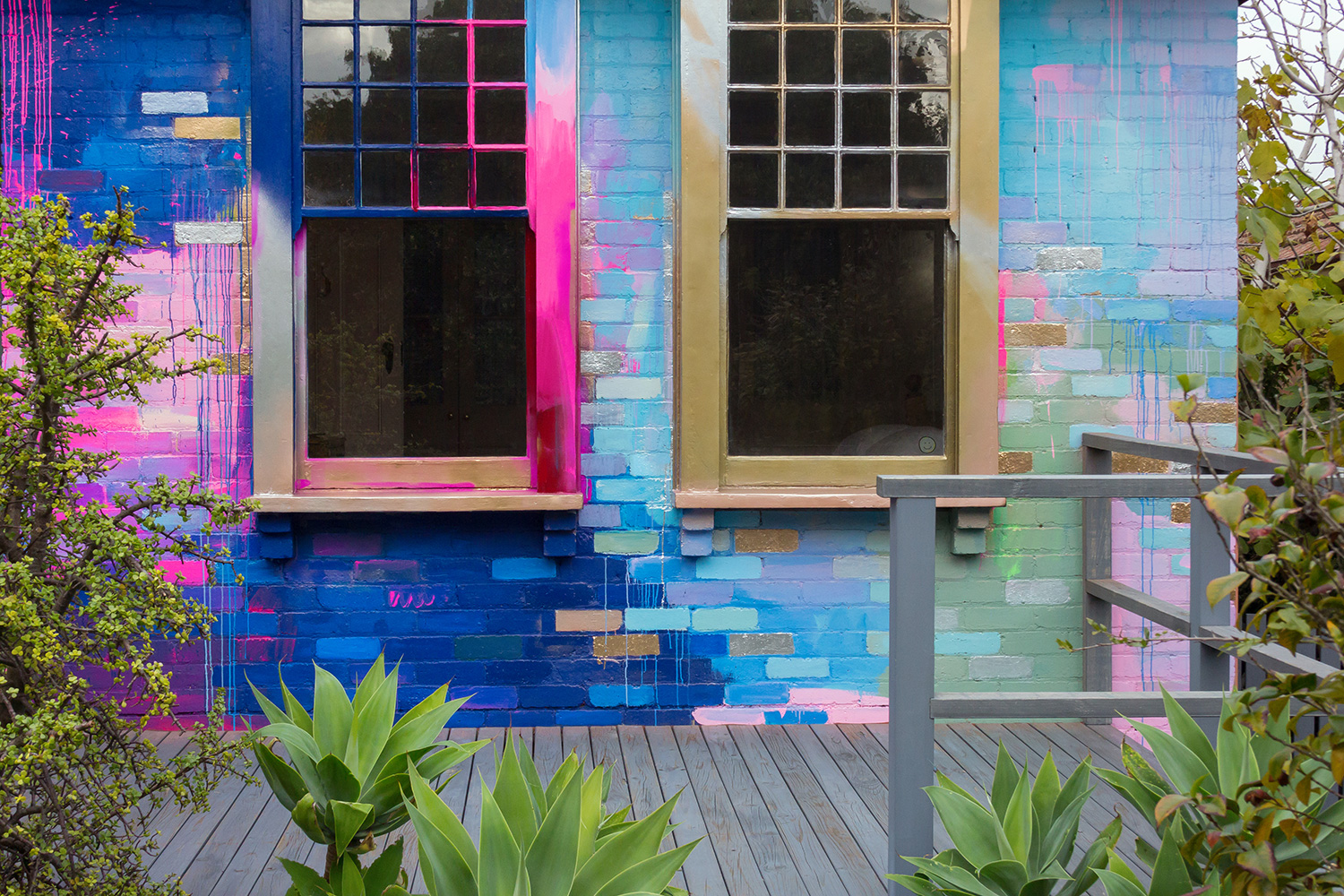 Vibrant abstract exterior mural that covers a residential home with a bright color palette of mostly pink, blue and metallic. Pops of color highlight the bricks and contrast with the garden foliage.