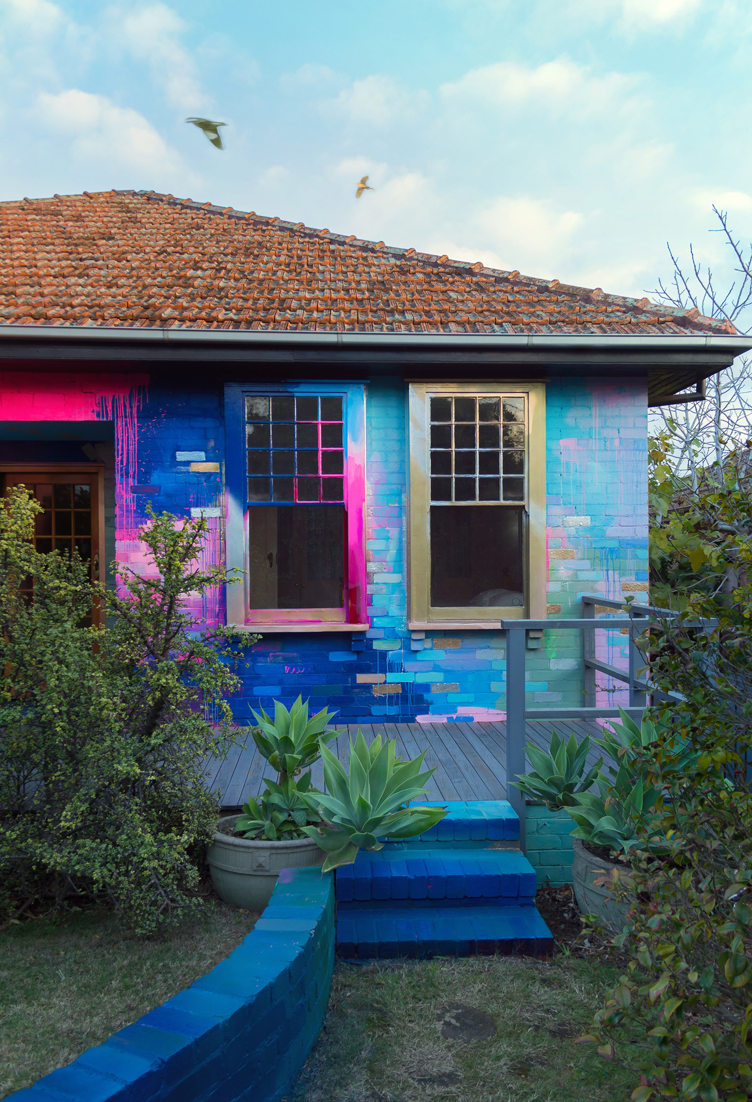Vibrant abstract exterior mural that covers a residential home with a bright color palette of mostly pink, blue and metallic. Pops of color highlight the bricks and create a sense of movement that leads the eye around the outdoor canvas and upwards to the sky.