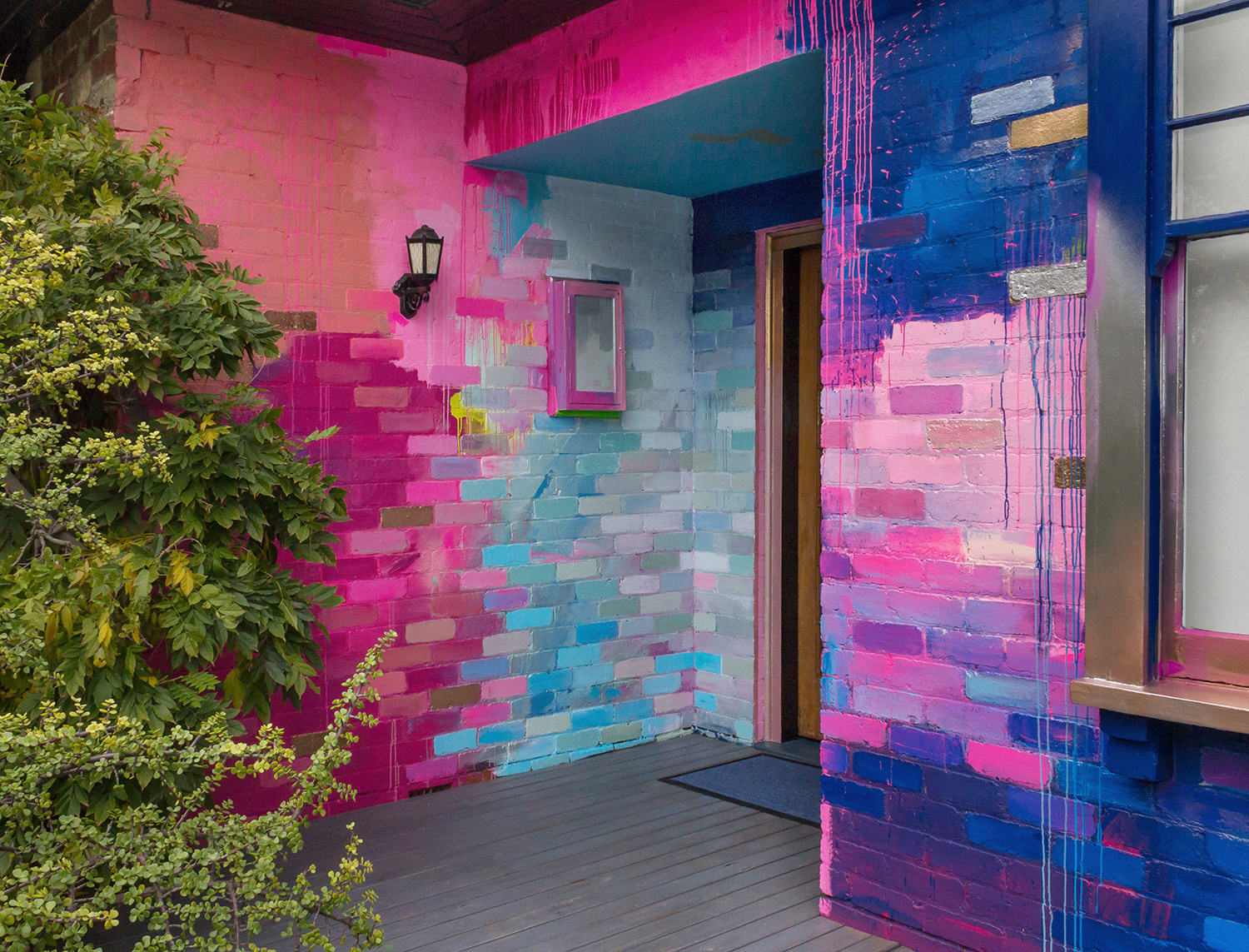 Vibrant abstract exterior mural that covers a residential home with a bright color palette of mostly pink, blue and metallic. Pops of color highlight the bricks and create a sense of movement that leads the eye around the outdoor canvas. Green foliage provides contrast to the bright color palette.