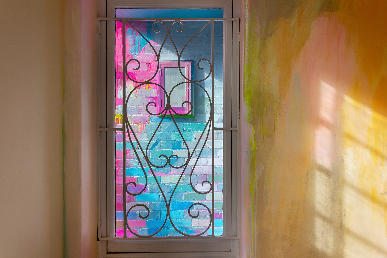A window provides a glimpse at a vibrant abstract mural on the wall outside.