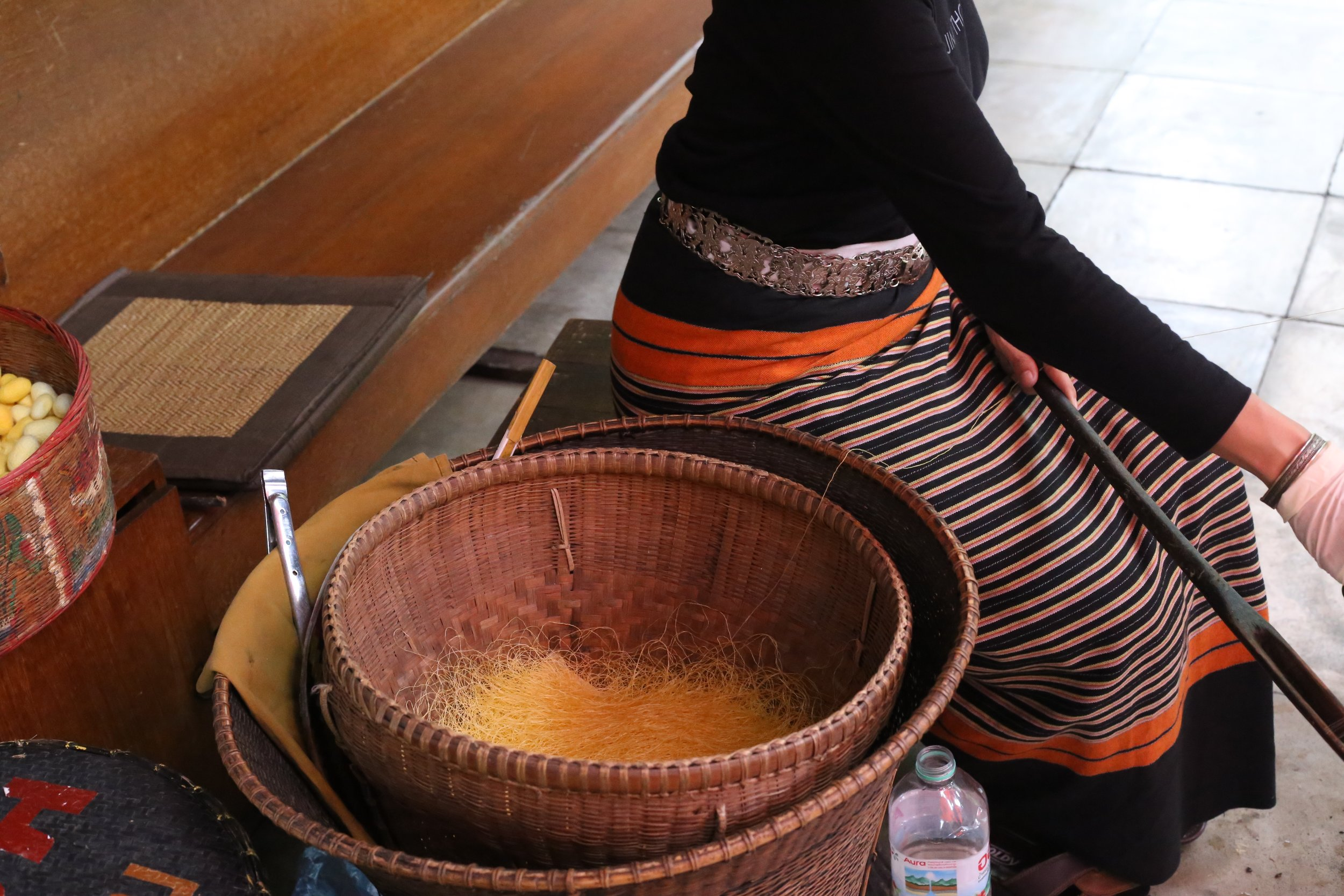 this woman was taking a basket of silk and using the spool to her right to spin it into scarves, shirts and other things for the jim thompson store and foundation.