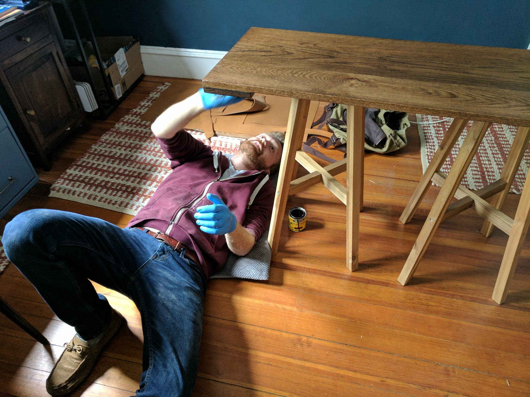 Laying on my dog's bed while I apply stain to the underside of the base.