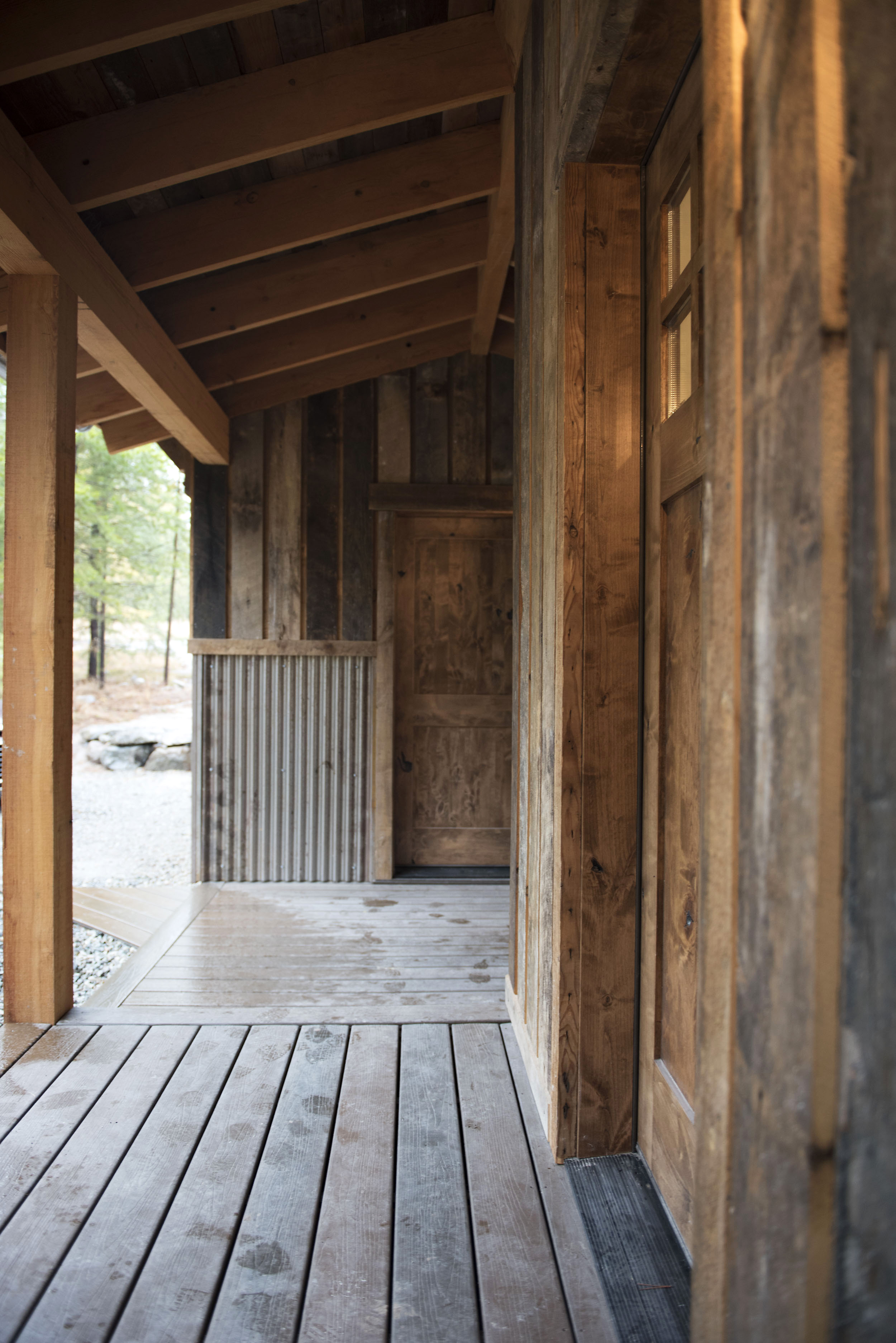 The mix of wood tones in the reclaimed siding makes it easy to introduce other wood accents like doors, beams, and decking.