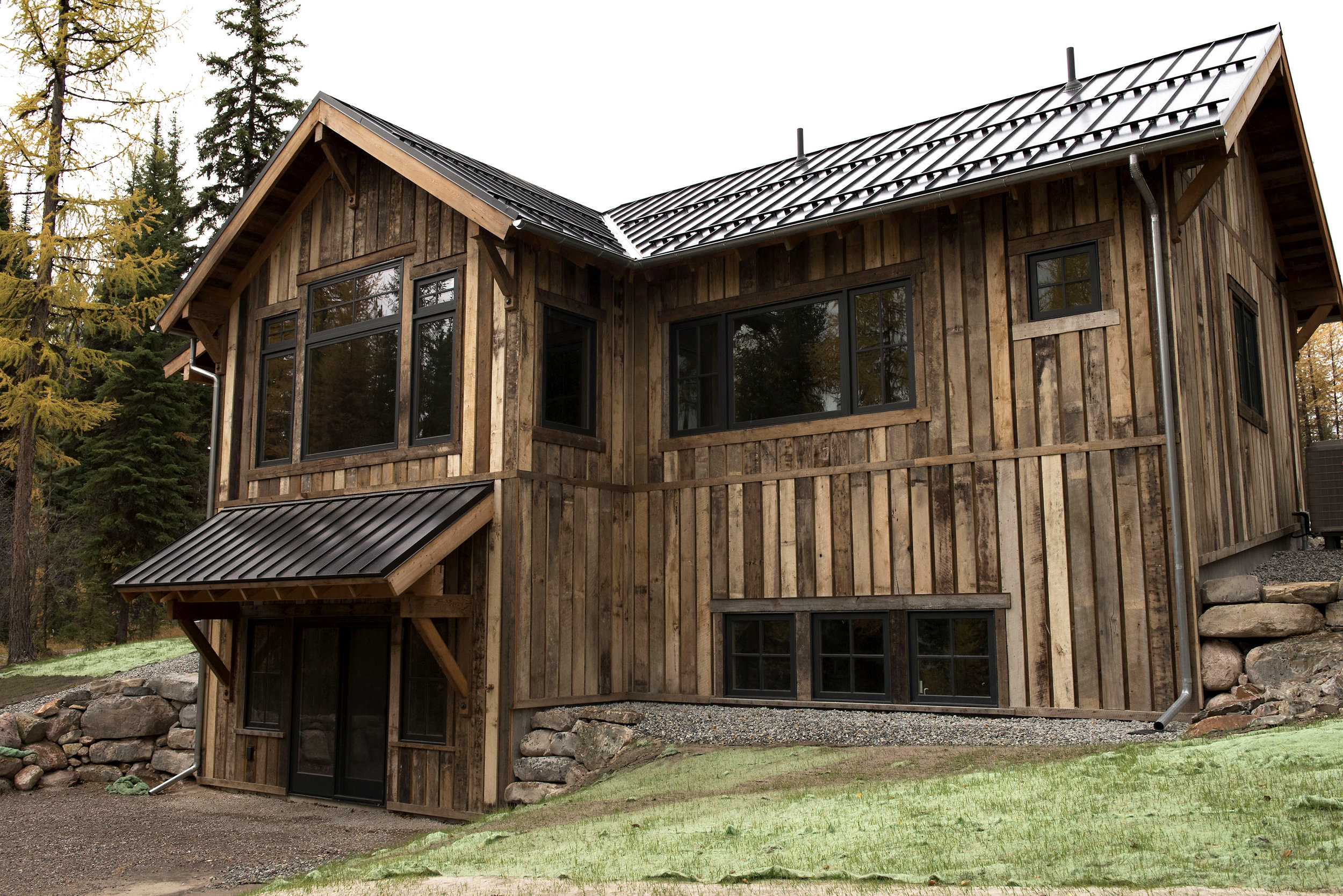 A lakeside view of the cabin reveals the reclaimed exterior window trim and metal roofing. Reclaimed window and floor trim was used throughout the interior of the home as well.