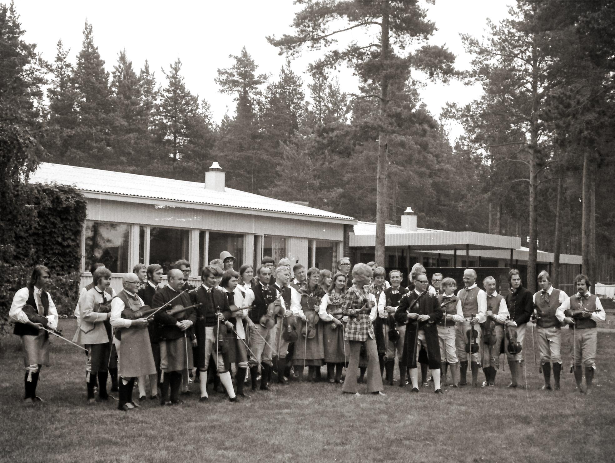 46 år innan Jonny Soling fick Knis Karl-stipendiet ses han här på bild tillsammans med just Knis Karl Aronsson och några andra spelmän som haft stor betydelse för honom. Bilden är från Husmodersskolan i Veteli i Österbotten, Finland. Där bodde två busslaster dalaspelmän i samband med Kaustinen Folk Music Festival i juli 1971. Jonny, tvåa från vänster, var färsk spelman. Han hade börjat spela i januari samma år trots att Erik Moraeus, fyra från väster i främre ledet, sagt att han var för gammal. Knis Karl står med långrock längst fram till höger. Med hatt i bakre raden finns en person som skulle bli Jonnys nära spelkompis och kollega vid Malungs folkhögskola i mer än 35 år, Kalle Almlöf. Till vänster om Jonny står hans lillebror Kalle. Till höger om Erik Moraeus ses Kungs Levi Nilsson, senare kurskamrat med Jonny på Musikhögskolan, och Olle Moraeus som tillsammans med andra unga Orsaspelmän inspirerade Jonny till att slå in på en ny musikalisk väg.Foto: Hans Bohm