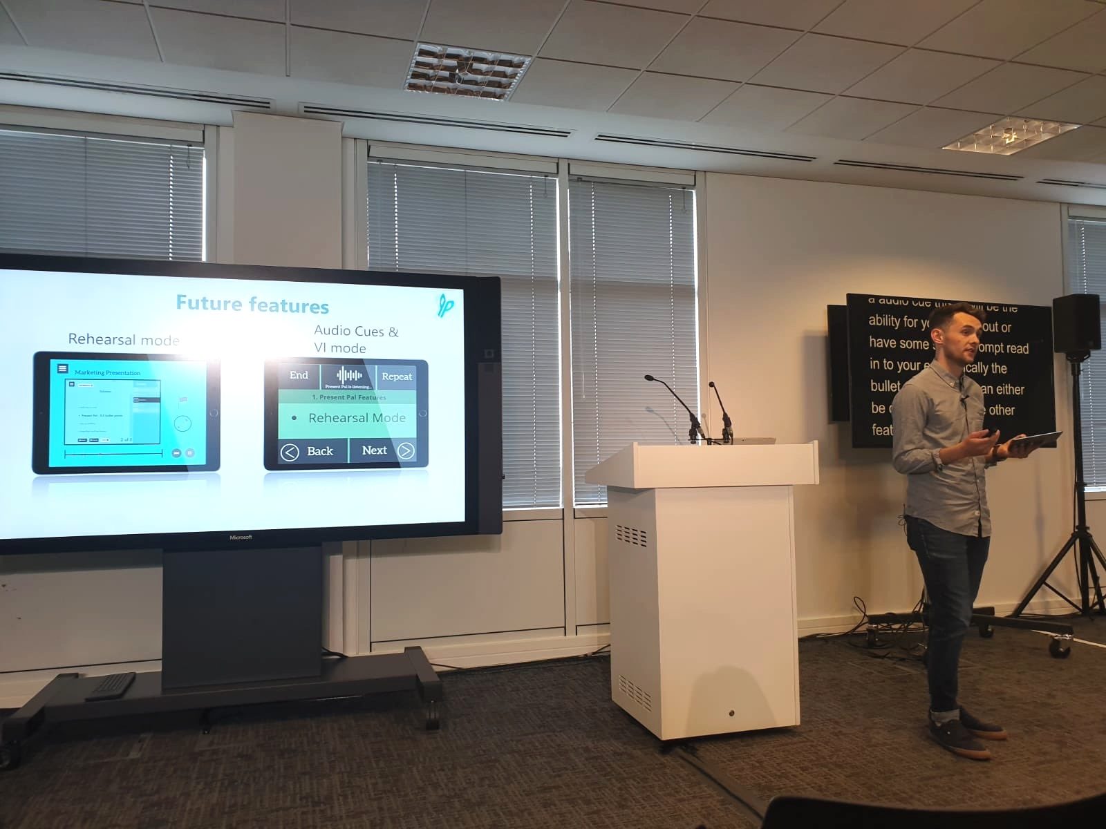 IMAGE: Chris Hughes presenting at Microsoft's #GAAD with PowerPoint slides and closed captions displayed on a TV screen.
