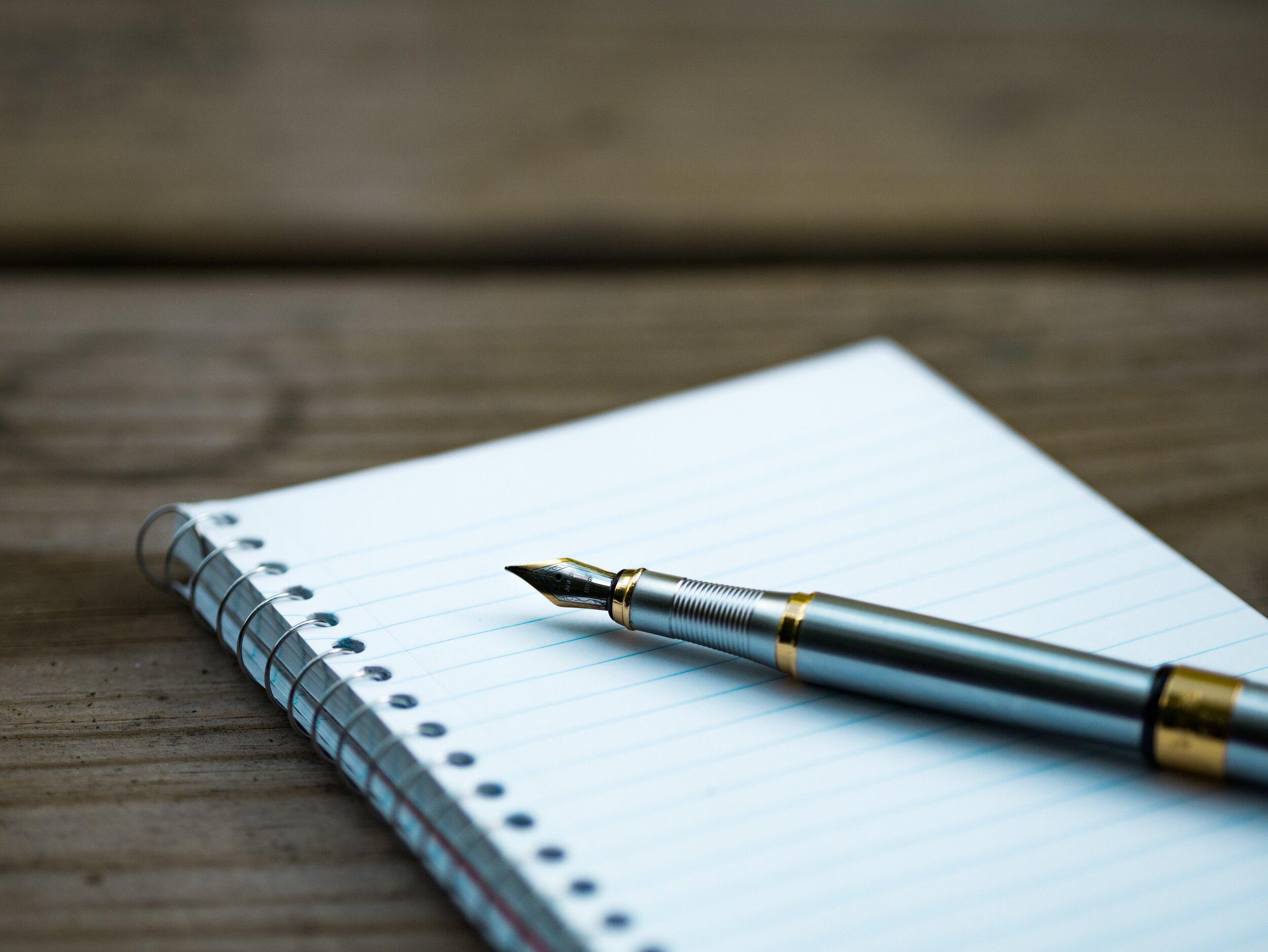 Image Description: A notepad with a pen on a wooden desk