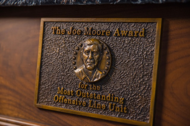 The trophy's bas-relief includes the likeness of Joe Moore, considered one of the greatest offensive line coaches in college football history