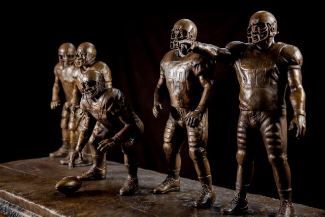 The trophy, with players that each stand more than two feet tall, will travel to each winning school's campus and stay there until the following year's winner is announced.