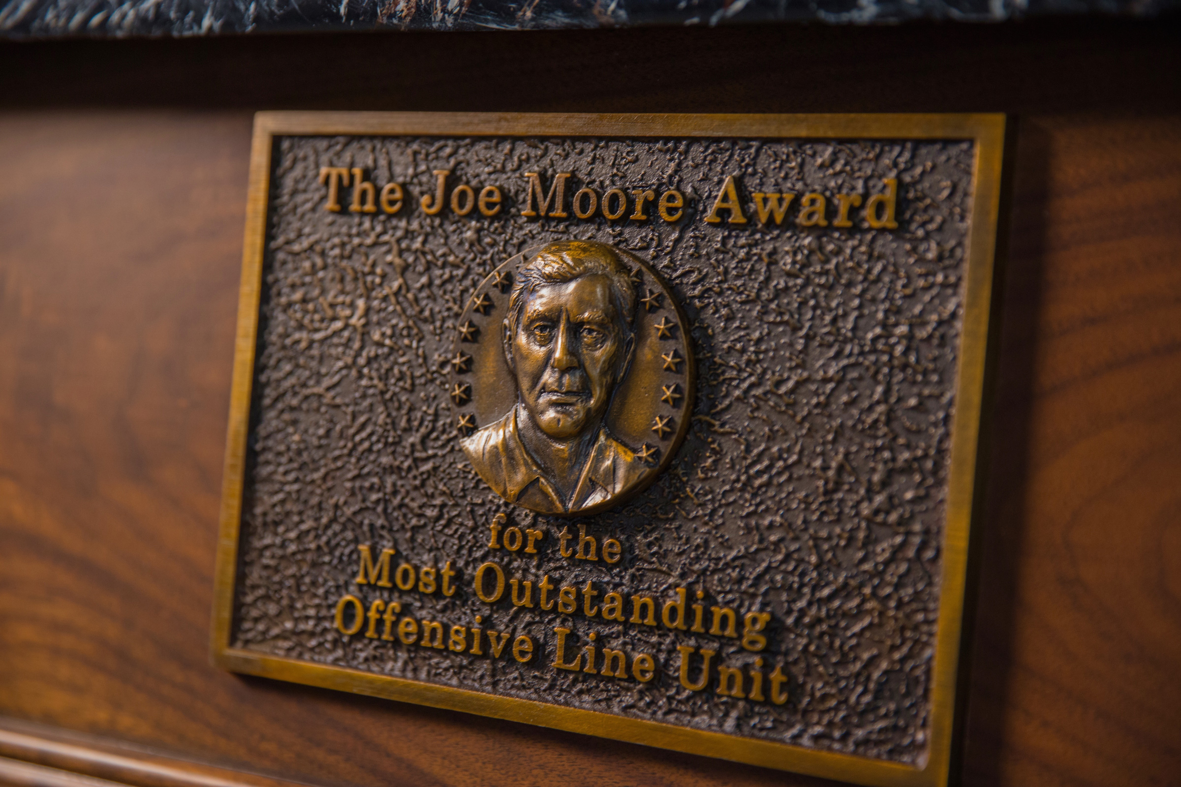 The trophy's bas-relief includes the likeness of Joe Moore, considered one of the greatest offensive line coaches in college football history.