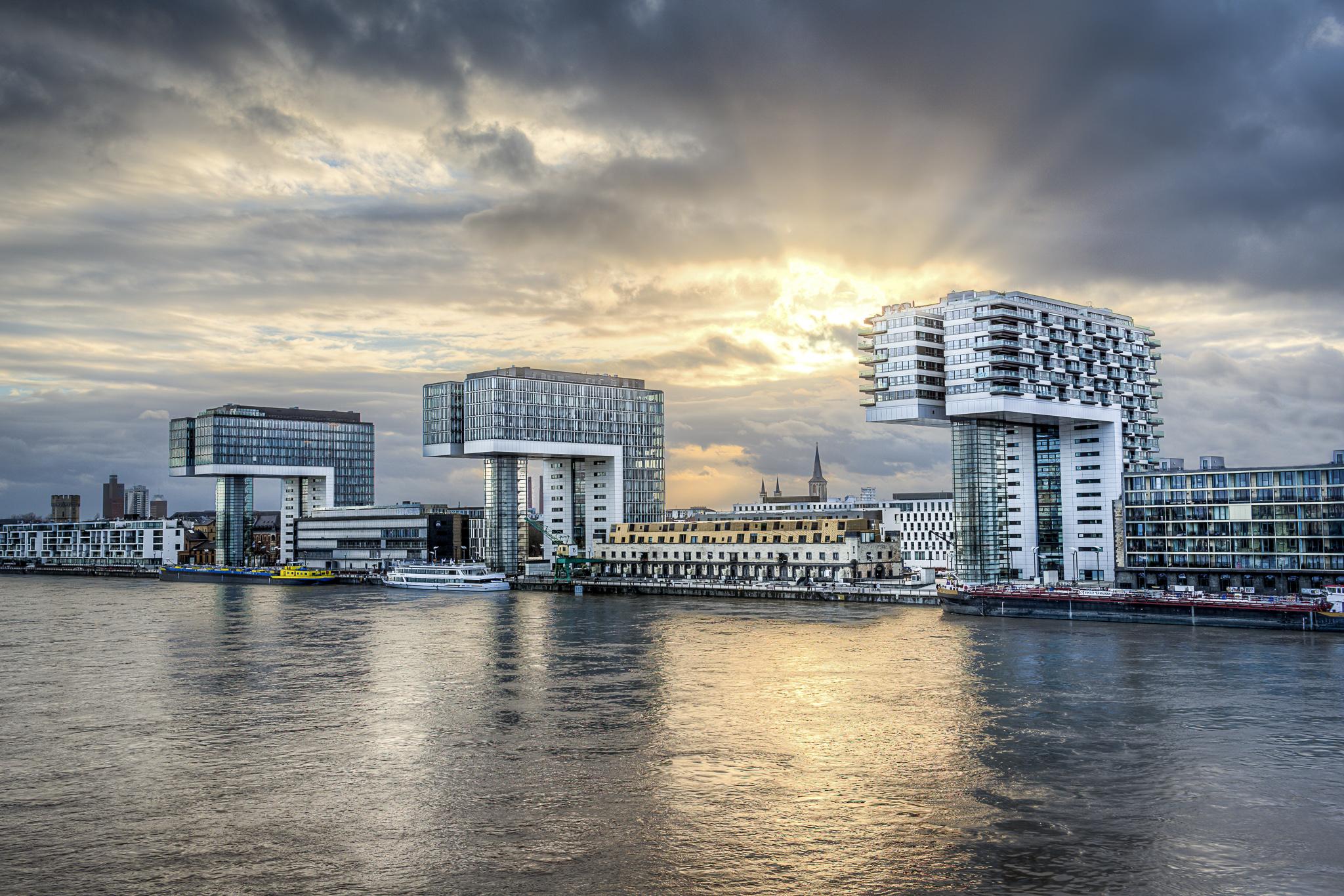 Kölner Kranhäuser im Sonnenlicht mit Rhein im Vordergrund