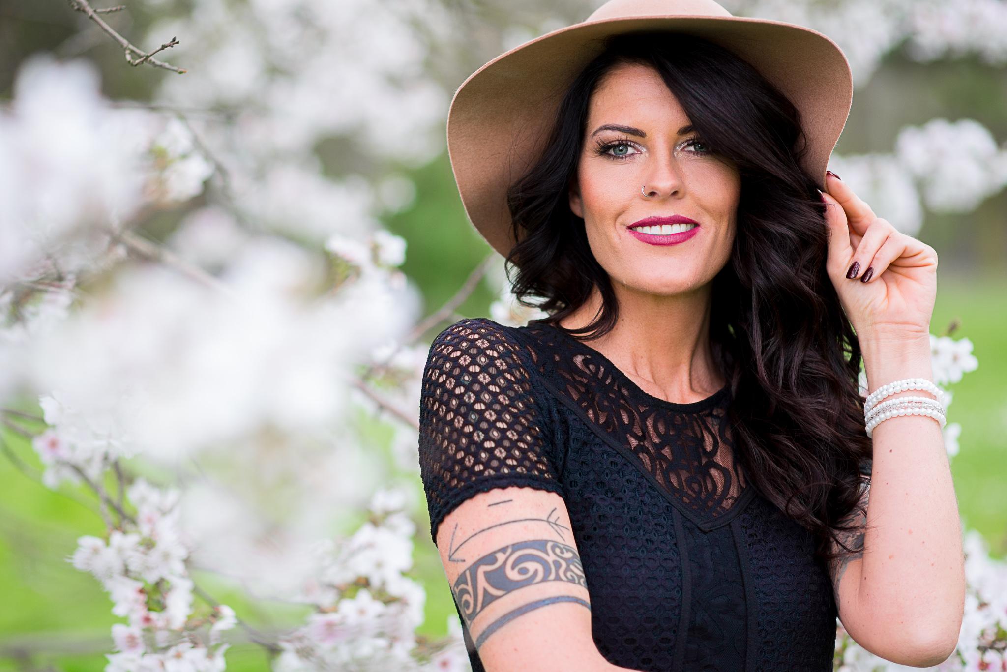 Portrait einer schönen Frau mit Hut und schwarzen Haaren im Forstbotanischengarten Garten in Köln