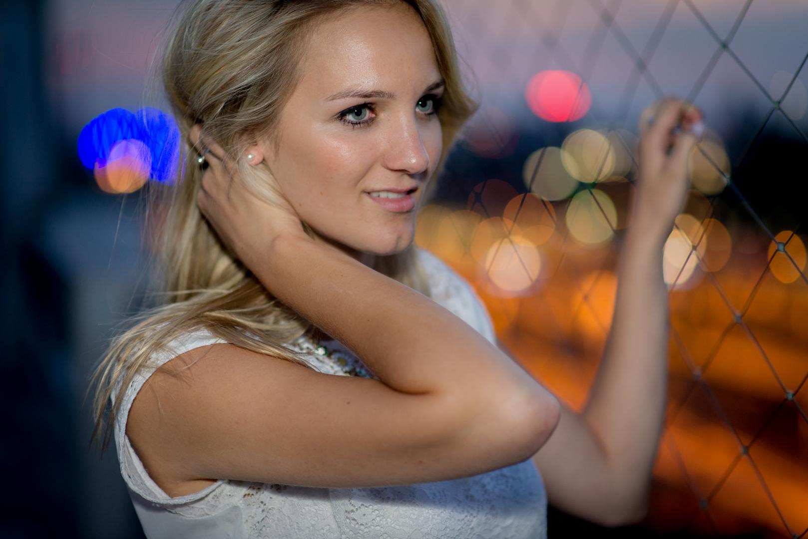 Portrait einer schönen Frau mit Lichter der Stadt in der Dämmerung in Köln