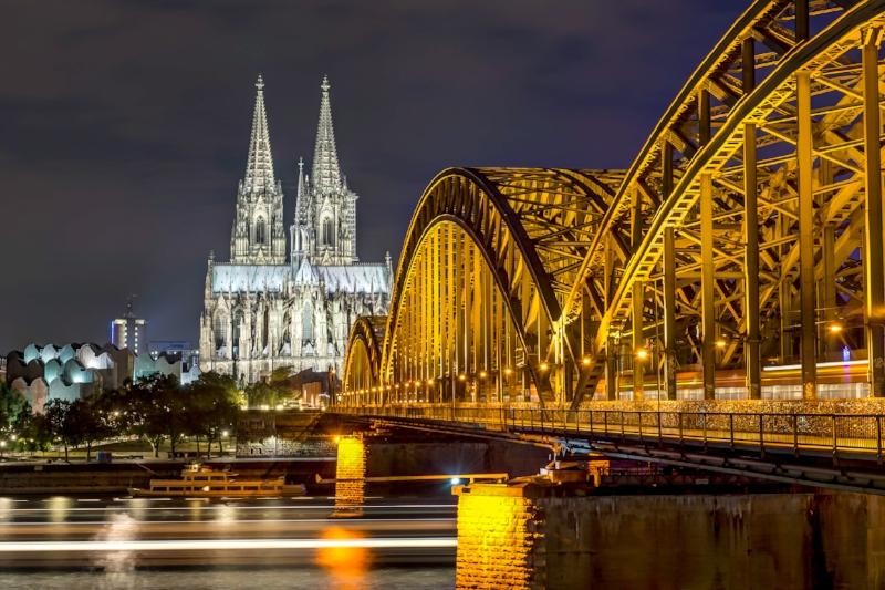 Kölner Dom mit Hohenzollernbrücke in der Nacht mit vorbeiziehe