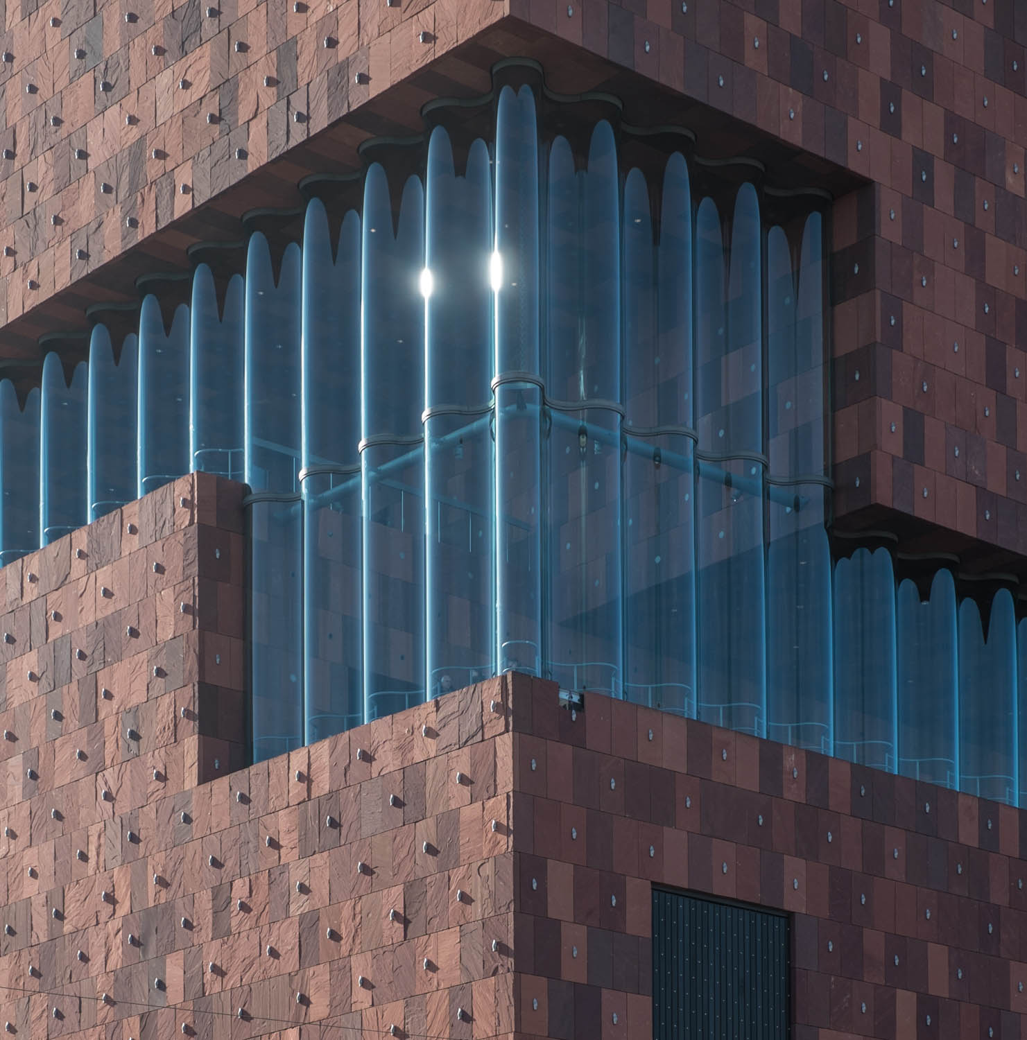 The delicate glass facade versus massive stone-cladded boxes.