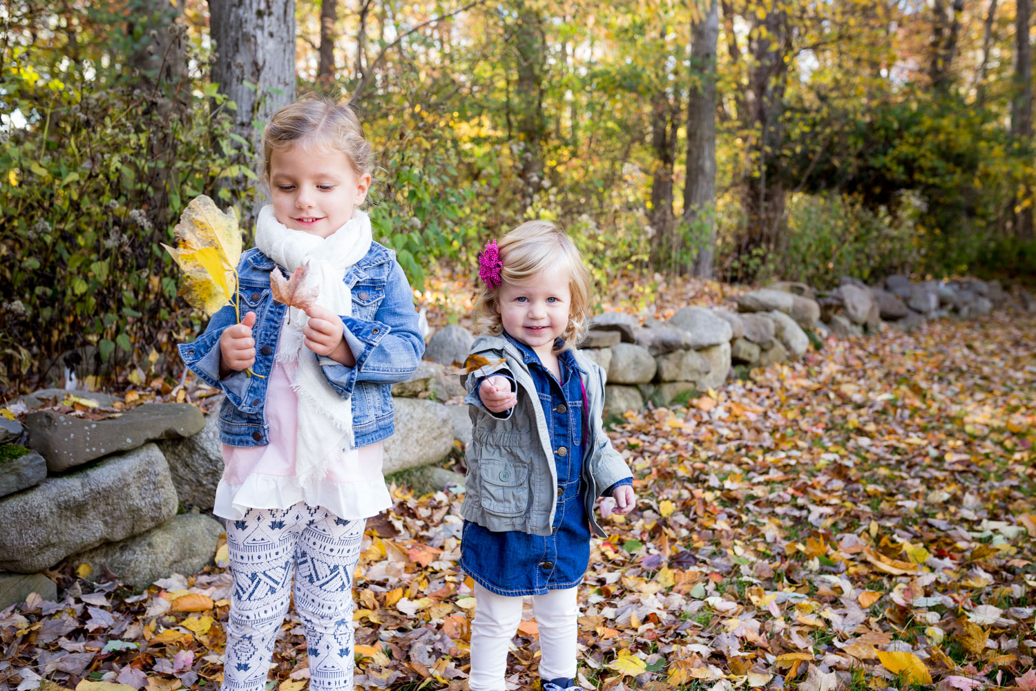 sisters playing in the leaves