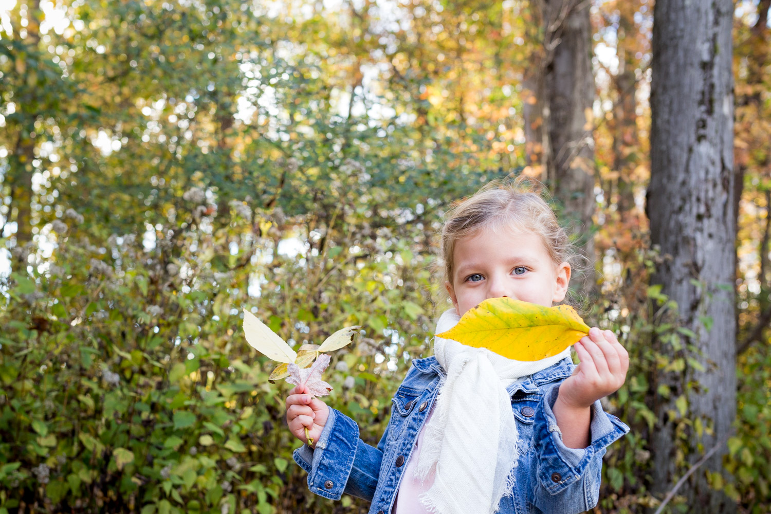 little girl hiding behind a yellow leaf