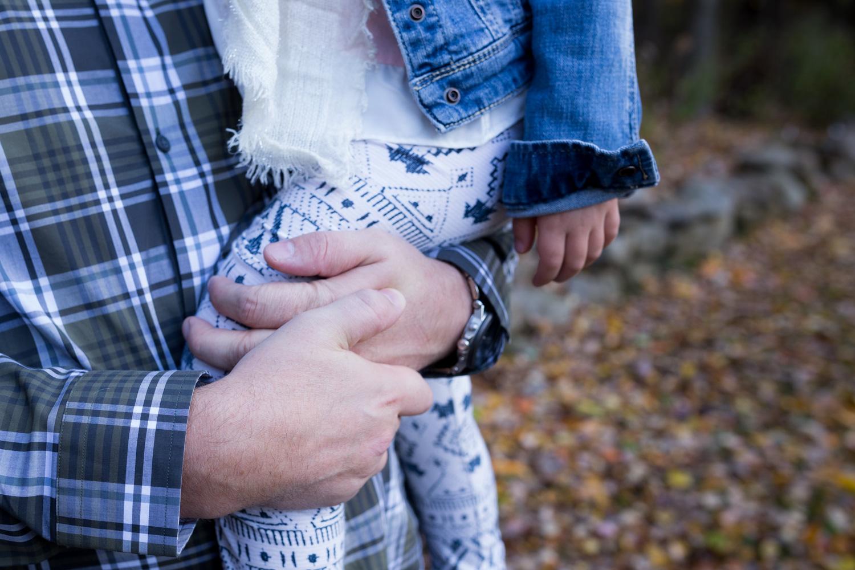 detail of daddy hugging his daughter close